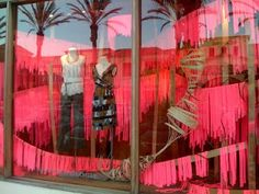 What an easy way to make a WOW consignment window display! TGtbT.com loves draping crepe paper streamers over fishing line for a dramatic display background/ foreground