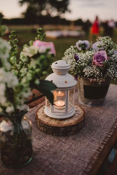 Image by - Lola Rose Photography - Lanterns & floral arrangements decor - Sottero & Midgely Lace Wedding Dress and Rachel Simpson Shoes for a rustic country wedding in a barn with delicate pastel flowers. Bridesmaids in Navy & Groom in Grey Bartlett and Butcher Suit.