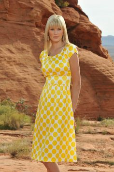 A bold bright dot print with a pleated scoop neckline and a classic A-line pleated skirt provides a flattering shape for all body types