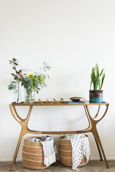 Gorgeous gold side table sideboard with brass finish, midcentury planter and potted snake plant, and sleek stylish woven storage baskets underneath. Such a great entryway piece, or would look great tucked in a living room corner.