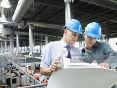 Stock Photo : Businessmen looking at blueprints in factory