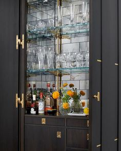 Chic kitchen features an dark brown bi fold doors opening to an espresso stained built-in bar ...