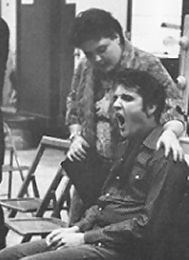 Elvis on movie set yawning. There is mama, Gladys, watching over her son.