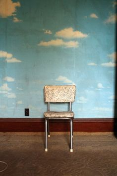 Becky's House. Sky wallpaper. Lonely chair. hint of a cord, in the lower left corner. black outlet. brown embossed rug, White vinyl dining chair with chrome legs. From the early 70s. cheap. A haze of brown breath on the light blue paper sky. A horizontal shadow on the carpet, in the foreground. or is it a stain.  Words: marvelitsky
