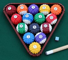 Fifteen colored and numbered balls, along with a LEGO pool stick. The little chalk-square is a lovely touch.