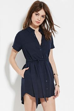 A cuffed short-sleeved mini shirt dress crafted from a linen-blend woven with a buttoned front, a basic collar, chest patch pockets, on-seam pockets, a curved hem, and a self-tie waist.