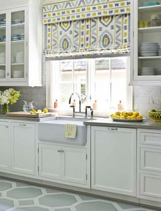 Ikat Roman shades in gray and yellow add punch to an all white kitchen.