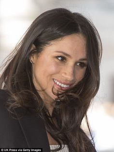 Meghan eschewed her customary messy bun and allowed her brunette locks to tumble around her shoulders