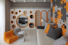 When Geometrix Design were planning this bedroom in a home in Moscow, Russia, they decided to create a fun and vibrant space that includes a custom wall unit along one wall, that serves as a storage system, a closet, and a play area.You can take the stairs or climb the rope up (with the help of additional circles that act as foot holes) to the the top of the closet which is covered in pillows, where you can sit and read a book, or make a fort.