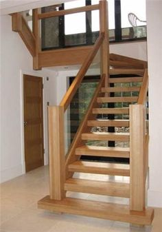 Oak staircase with open risers and glass paneling. Square newel posts. Donegal, Ireland