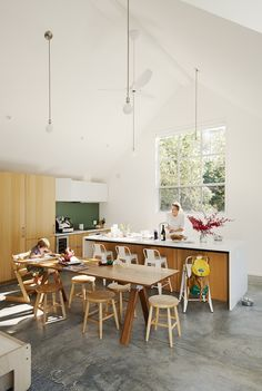 Formerly a one-bedroom cabin, the Mill Valley, California, home of Tim and Stefanie Rosa more than doubled in size after a renovation and addition by Pfau Long Architecture. The high-ceilinged kitchen-living-dining room is outfitted with white oak casework by Henrybuilt. Leo, five, sits in a Tripp Trapp chair at a custom dining table.