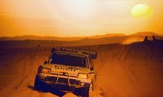 A Peugeot 205 Turbo T16 powers through the sand as the sun sets