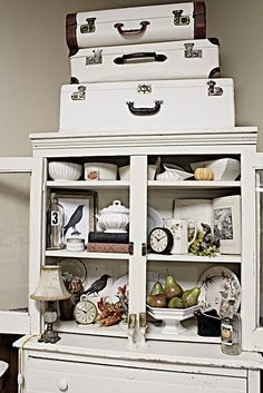 OMG! Love how she painted these vintage suitcases white, using plain old latex interior house paint! ~ love this vignette