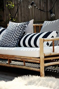 nautical patio  black and white and navy striped pillows on simple patio furniture with woven blankets