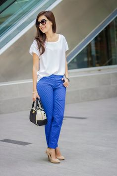 White top, blue patterned pants, neutral heels.