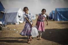 Iraqi children carry water to their tent at a temporary displacement camp set up next to a Kurdish checkpoint on June 13 in Kalak, Iraq. Thousands of people have fled Iraq's second city of Mosul after it was overrun by ISAS (Islamic State of Iraq and Syria) militants. (Dan Kitwood/Getty Images)