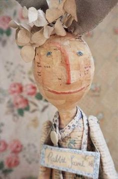 Julie Arkell.  Words and phrases I hear, read and put together inspire my creatures. I use paper and glue to mould the figures. Their arms and legs can be papier mache or plastic, taken off old dolls and re-assembled. The clothes they wear are knitted, sewn and crocheted, with parts of their story embroidered on to them. Houses, boats, trees, chairs and prams are constructed to make up their habitat.  See also http://www.earthangelstoys.com/html/julie_arkell_-_paper_mache.html