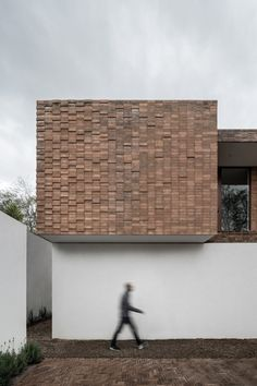 Clay brick and concrete Mexican house is set around a cactus tree
