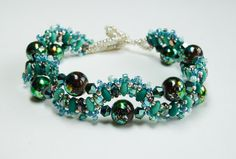 This striking handmade bracelet features a swirl of superduo beads in shades of turquoise, embellished with bicone crystals, multi colour