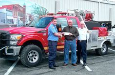 Standing in front of Convoy Fire Dept. brand new fire truck is Firefighter Colin Harting (committee chairman) presenting the Mayor of Convoy, Brad Guest, with a check from the Convoy Fire and EMS membership for the payoff of the new Quick Response Fire Truck. On the right is Convoy Fire Chief Don Wilson observing the presentation. (Photo submitted)