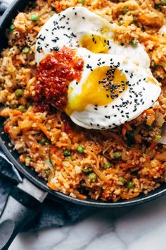 Kimchi Fried Rice FTW! Cauliflower rice, frozen peas and carrots, fresh garlic and ginger, soy sauce, chili paste, a forkful of kimchi, and finished with a runny yolk waterfall. A new kind of comfort food. #friedrice #kimchi #cauliflower #veggies #vegetarian #dinner #spicy #healthy #mealprep   pinchofyum.com