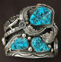This traditional 1970's bracelet was hand wrought by Orville Tsinnie, from Shiprock, New Mexico. Orville is a master silversmith and has won many awards for his outstanding silver and stone designs. Over the past 30 years Orville has used our Morenci