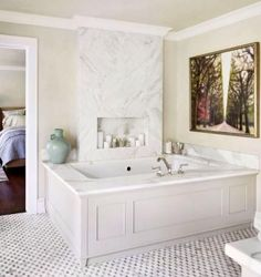 Wood panels and marble create a sumptuous surround for the Kohler whirlpool tub with a polished-nickel Rohl tub filler. A marble cutout is ideal for placing bath soaps, candles, or a glass of wine! - Traditional Home ® / Photo: Werner Straube / Design: Rosemary Merrill