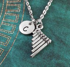 This listing is for a personalized pan flute necklace with a hand-stamped initial charm. Youll be able to choose your initial from the drop-down menu,