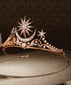An antique diamond tiara, circa 1900. The centre of sunburst star and crescent moon motifs entirely set with cushion-shaped diamonds, graduating in size towards the centre, above a larger similarly cut diamond, between a scrolling frame set with old brilliant-cut diamonds, accented by two smaller similarly set sunburst stars, brooch, hair ornaments, ring and tiara fittings and screw supplied, fitted case by Cav. Vincenzo Giura Giojelliere, Napoli. #antique #tiara