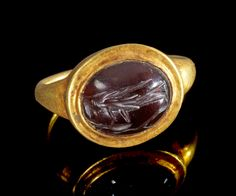Golden ring with gemstone made of garnet depicting Victory holding a shield in front of a tree. Roman, 2nd - 3rd century A.D. Intact.