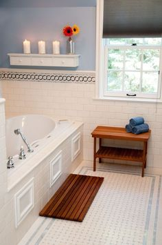 White And Blue Bathroom with Alcove Bathtub containing: Wooden Bath Mat with Chrome Finish Faucet also Patterned Floor Tile plus Tile Wainscoting together with Wall Mount Shelving with Decorative Flowers also Gray Window Shade plus Wood Framed Window