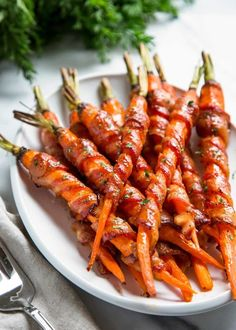 These Bacon Wrapped Carrots get sprinkled with black pepper and roasted, then basted with a maple Sriracha sauce until crispy. So easy and good! keviniscooking.com