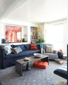 In the living room of Eric Hughes and Nathan Turner's home in Malibu, California, the sofa, designed by Turner, and armchair have slipcovers of Ralph Lauren Home fabrics. The rug is by Langham & Fine, and the wall and ceiling paneling are painted in Benjamin Moore's Super White. - ELLEDecor.com