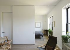 A seamless sliding door by CS For Doors—accented by Mockett hardware—separates the master bedroom from the living room and doubles as a backdrop for a projector. Tagged: Doors, Interior, Wood, and Sliding Door Type. Hanging Room Dividers, Sliding Room Dividers, Sliding Wall, Sliding Partition Doors, Cavity Sliding Doors, Door Dividers, Small Space Living, Tiny Living, Small Spaces