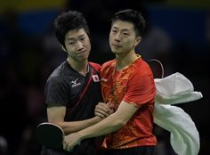 China's Ma Long (R) embraces Japan's Jun Mizutani after winning their men's…