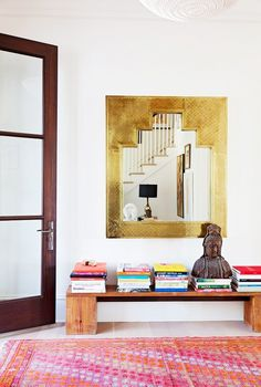 Gold framed mirror, wooden bench, colorful rug, glass door