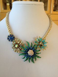 Repurposed vintage flower brooch necklace, flower statement necklace, vintage flower brooch and earring assemblage, bib necklace. $50.00, via Etsy.