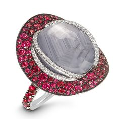A stellar 22.60 carat Burmese grey star sapphire holds intrigue within its smoky depths. Orbited by brilliant-cut diamonds and surrounded by red spinels and rubies set in 18-karat white gold, it's an accessory like no other.