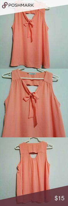 """Peach tank with bow and cutout Beautiful peach shirt. Cutout in back. Pussy bow in front.  Tank. Flowy bottom. ***there are a few snags on the back that I couldn't get to show up. No runners or holes or stains.  Measures lying flat- Waist-21"""" Length 25"""" Maurices Tops Tank Tops"""