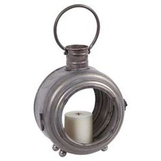 """Perfect on your tablescape or in a rustic-chic vignette, this handsome candleholder features a round metal frame and glass panels. Product: CandleholderConstruction Material: Metal and glassColor: SilverFeatures: Porthole-inspired designOne handleAccommodates: (1) Candle - not includedDimensions: Small: 14"""" H x 9"""" W x 6"""" DLarge: 17"""" H x 11"""" W x 7"""" D"""