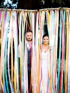 Buy spools of ribbon in variations of two to three inches, and make sure they are in shades of your wedding colors. Tie seven- to eight-foot strands to a branch, and suspend it from the ceiling or outdoor trees. The end result will make for a whimsical photo backdrop!