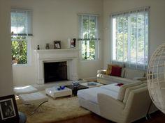 Sala de estar com lareira em madeira laqueada, janelas guilhotinas em alumínio, ambiente leve e agradável com vista para a mata.