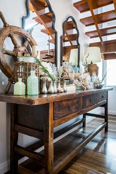Hmm... #nautical foyer idea? Advantage Property Styling, Collector's Table, Console, Coral, Glass, Bottles, Mirrors, Lamps, Bell Jars, Wood, Rustic, Coastal, Treasure, Ship's Wheel