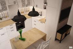 Bardzo funkcjonalna aranżacja małej kuchni z wyspą, która pełni jednocześnie funkcję stołu śniadaniowego. Industrialne lampy wiszące o czarnych kloszach dobrze współgrają ze skandynawskim klimatem, jaki dominuje we wnętrzu. Białe szafki i drewno tworzą przyjemny naturalny charakter całego wnętrza.
