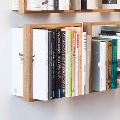 Schwebende Bücher –diesen Eindruck gewinnt man beim Regal b. Ob Kunstband oder Taschenbuch - einzig der massive Holzrahmen scheint den Büchern Halt zu geben. Ohne Bücher lüftet sich das Geheimnis, eingelassene Edelstahlwinkel halten die Konstruktion an der Wand. Aus heimischer Eiche und Edelstahl in Hamburg gefertigt. Als Einzelstück oder Regalwand, im Rastermaß oder nach eigenen Vorstellungen montiert, entstehen mit b kleine oder große, symmetrische oder eigensinnige Regalwände. Jede für…
