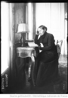 Mme Franck [femme assise à une table, lisant] : [photographie de presse] / [Agence Rol] - 1913