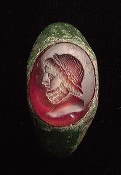 A ROMAN BRONZE INTAGLIO RING, ca. The ring set with a large x 16 mm) and fine red carnelian deeply carved with the diademed bust of a bearded male, perhaps Zeus.