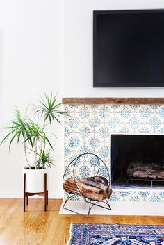 Fireplace with hand painted tiles and midcentury modern plant stand.