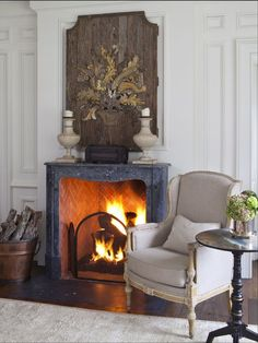 a vintage fireplace is used to make the living room cozier and is styled with a large wooden artwork #livingroom #fireplace