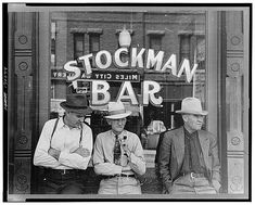 Miles City, Montana. Stockmen in front of a bar on main street, 1939